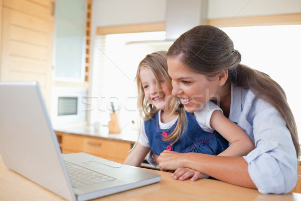 Smiling mother and her daughter using a laptop in their kitchen Stock photo © wavebreak_media