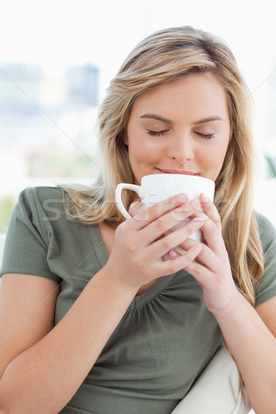 A woman holding a cup up to her nose, taking in a smell of the cups contents in front of her. Stock photo © wavebreak_media