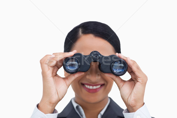 Stock photo: Close up of smiling saleswoman using spy glasses against a white background