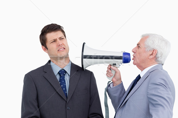Close up of mature businessman with megaphone yelling at colleague against a white background Stock photo © wavebreak_media