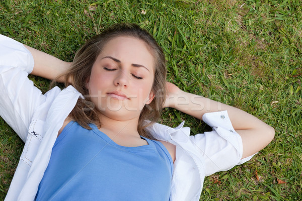 Young relaxed girl napping in a parkland with her hands behind her head Stock photo © wavebreak_media