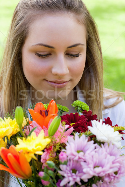 Young relaxed blonde girl smelling a beautiful bunch of flowers while closing her eyes Stock photo © wavebreak_media