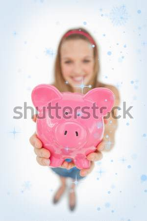 Fisheye view of a young woman tending a piggy-bank against white background Stock photo © wavebreak_media