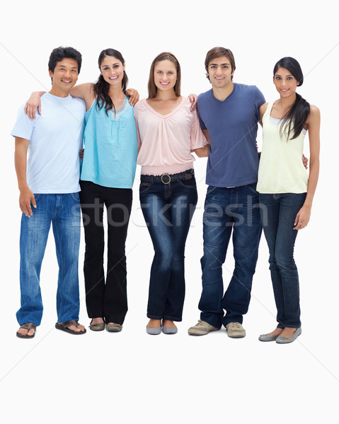 Friends smiling arm in arm against white background Stock photo © wavebreak_media