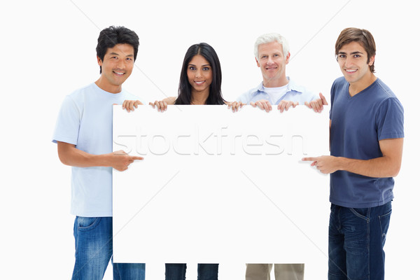 People in jeans holding and showing a big sign against white background Stock photo © wavebreak_media