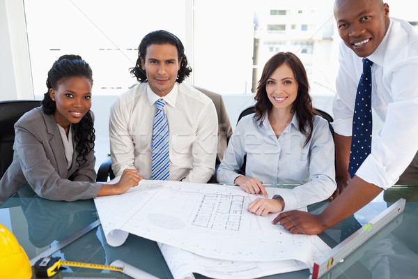 Stock photo: Business team smiling while working on a project in a bright meeting room