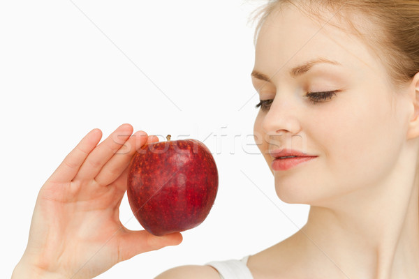 Woman holding an apple while looking at it against white background Stock photo © wavebreak_media