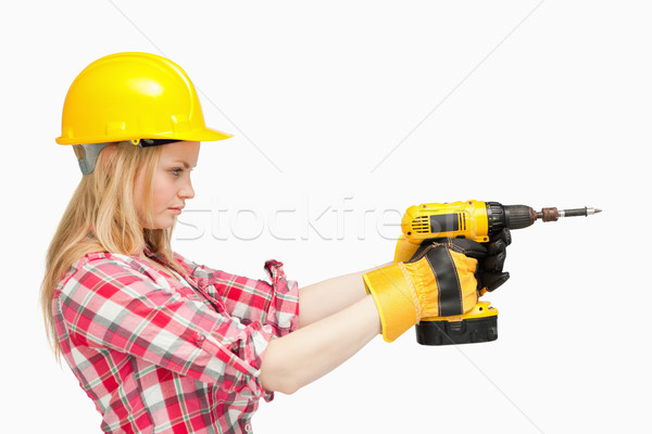 Serious woman using an electric screwdriver against white background Stock photo © wavebreak_media