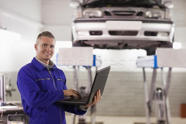 Mécanicien tapant portable garage heureux métal Photo stock © wavebreak_media