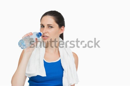 Sportswoman with a towel drinking water against white background Stock photo © wavebreak_media