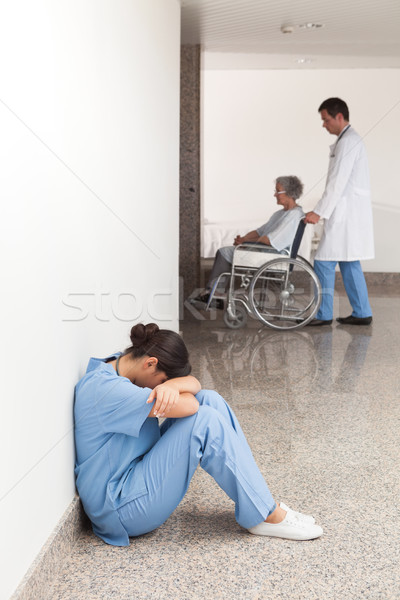 Nurse sitting on the ground in the hallway of the hospital with head in hands Stock photo © wavebreak_media