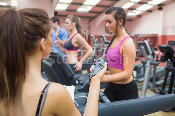 Female instructor using stopwatch in the gym Stock photo © wavebreak_media