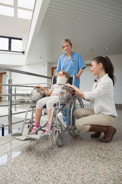 Mother crouches next to her child in wheelchair with nurse pushing it in hospital corridor Stock photo © wavebreak_media