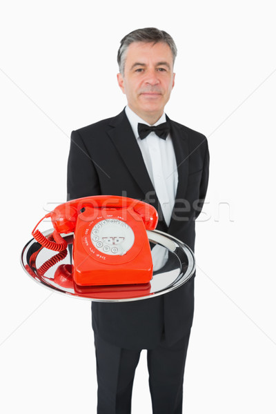 Well-dressed waiter holding a red phone on a silver tray on white background Stock photo © wavebreak_media