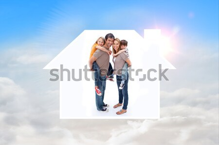 Smiling family standing with a black house illustration with energy rating Stock photo © wavebreak_media