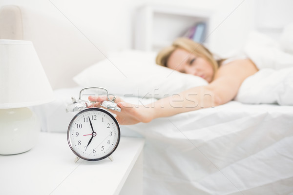 Irritated young woman in bed extending hand to alarm clock Stock photo © wavebreak_media