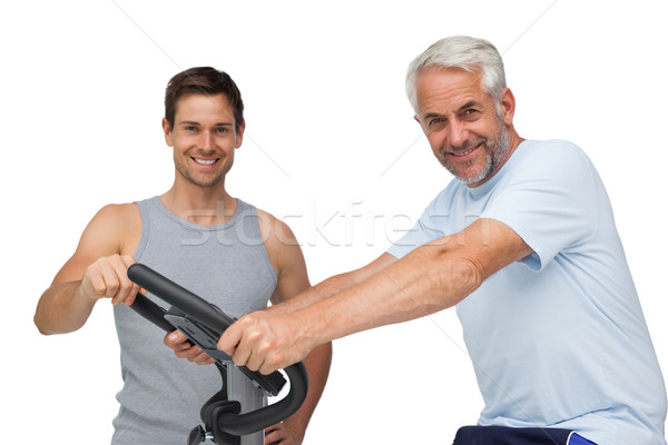Happy mature man on stationary bike with trainer Stock photo © wavebreak_media