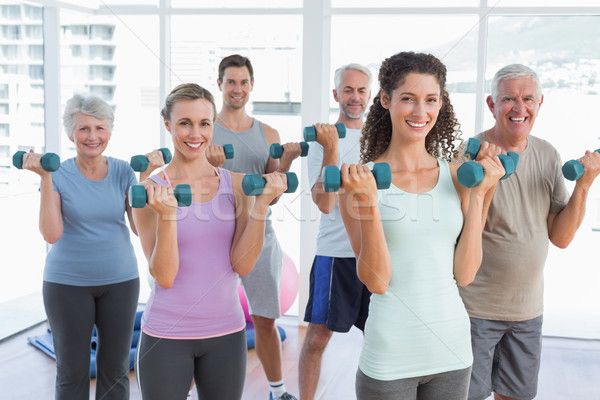 Class exercising with dumbbells in gym Stock photo © wavebreak_media
