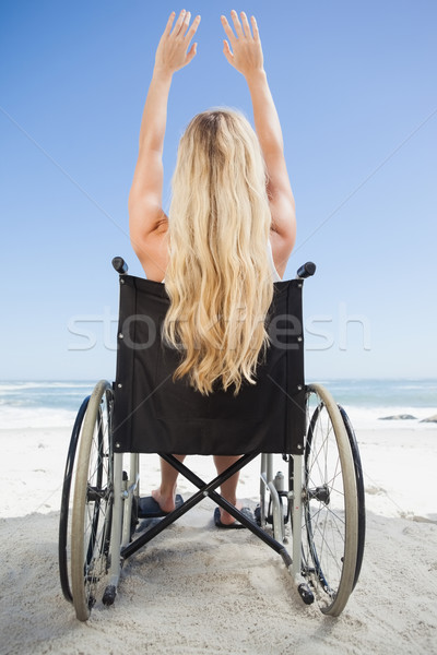 Wheelchair bound blonde sitting on the beach with arms up Stock photo © wavebreak_media