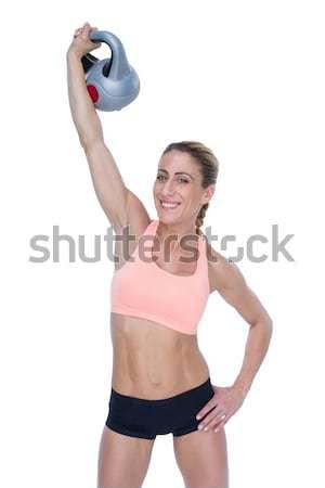 Female blonde crossfitter lifting kettlebell above head smiling  Stock photo © wavebreak_media