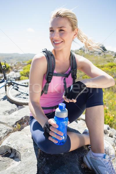 Fit pretty cyclist taking a break on rocky peak  Stock photo © wavebreak_media