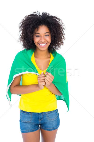 Pretty girl in yellow tshirt and brazilian flag smiling at camer Stock photo © wavebreak_media