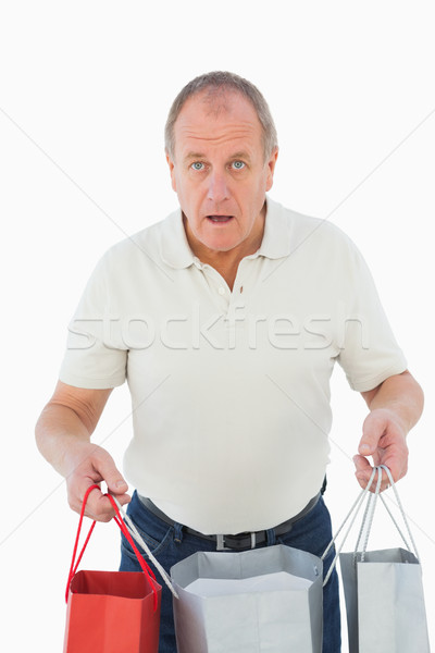 Mature man feeling buyers remorse holding bags Stock photo © wavebreak_media