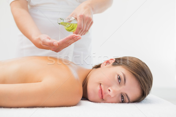 Attractive woman getting massage oil on her back Stock photo © wavebreak_media