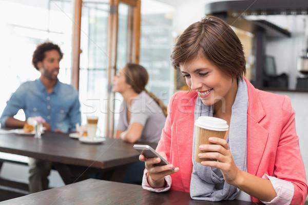 Pretty brunette sending a text drinking coffee Stock photo © wavebreak_media