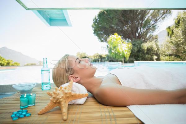 Beautiful woman lying on massage table at spa center Stock photo © wavebreak_media
