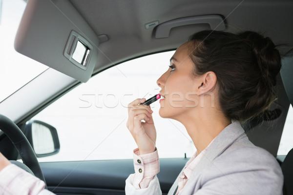 Femeie oglindă ruj conducere maşină femeie Imagine de stoc © wavebreak_media
