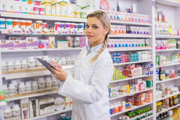 Pharmacy intern writing on clipboard Stock photo © wavebreak_media