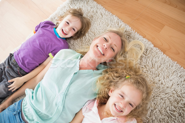 Happy mother and children lying on rug Stock photo © wavebreak_media