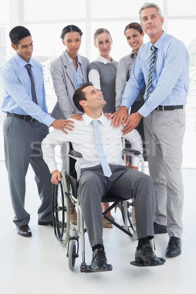Affaires fauteuil roulant collègues regarder caméra bureau Photo stock © wavebreak_media