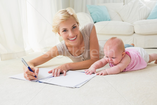 Stock photo: Smiling blonde mother with her baby girl writting on a copybook
