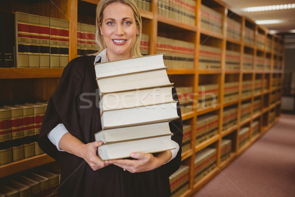 Smiling lawyer holding heavy pile of books standing Stock photo © wavebreak_media