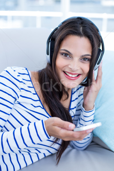 Smiling beautiful brunette relaxing on the couch and listening m Stock photo © wavebreak_media