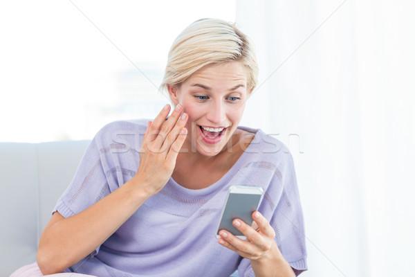Csinos szőke nő sms chat mobiltelefon nappali ház Stock fotó © wavebreak_media