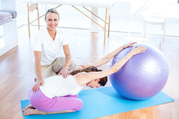 Trainer helping woman with exercise ball Stock photo © wavebreak_media