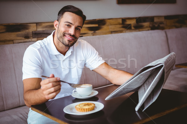 Young man having cup of coffee and eating pastry Stock photo © wavebreak_media