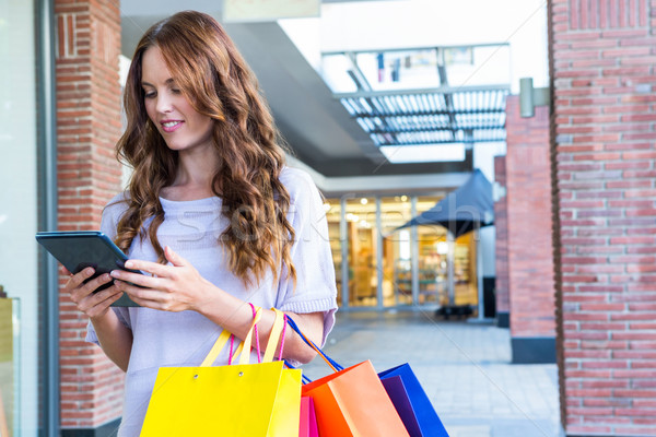 Pretty woman shopping at the mall using tablet Stock photo © wavebreak_media