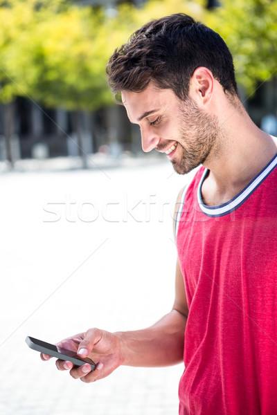 Mosolyog jóképű atléta küldés szöveg napos idő Stock fotó © wavebreak_media