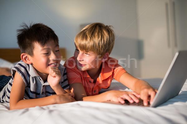 Mosolyog testvérek laptopot használ ágy hálószoba számítógép Stock fotó © wavebreak_media