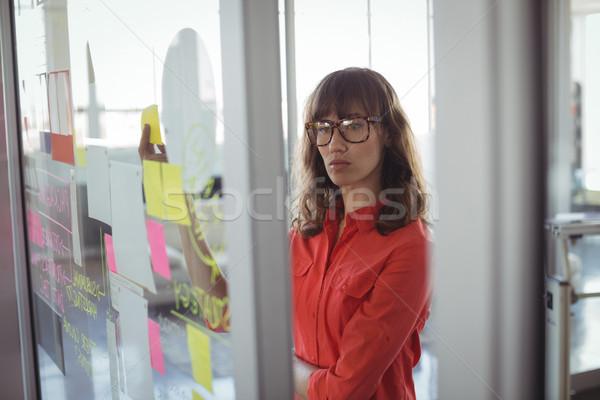 Figyelmes üzletasszony néz tapadó jegyzetek iroda Stock fotó © wavebreak_media