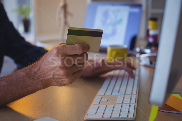 Cropped businessman shopping online with credit card at office Stock photo © wavebreak_media