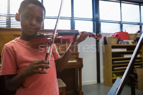 Portrait of smiling boy playing violin while standing in classroom Stock photo © wavebreak_media