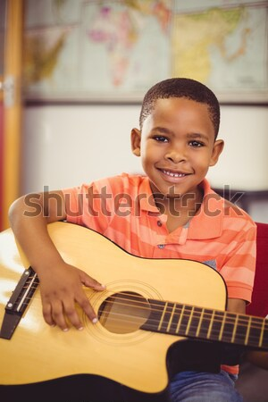 Portrait of boy holding guitar in class Stock photo © wavebreak_media