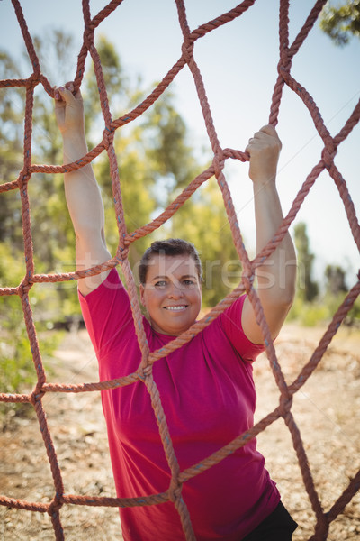 Portrait of happy woman climbing a net during obstacle course Stock photo © wavebreak_media