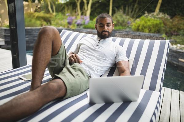 Férfi laptopot használ megnyugtató társalgó szék veranda Stock fotó © wavebreak_media