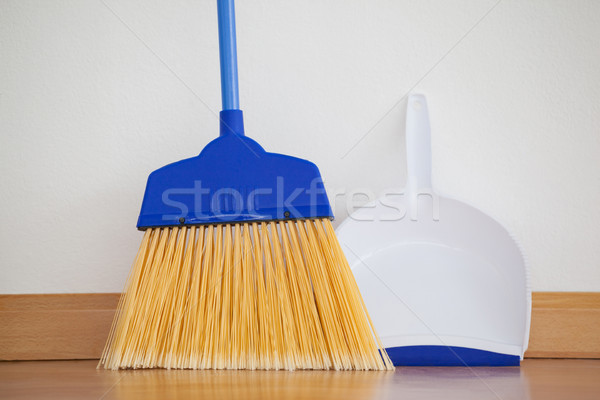 Dustpan and sweeping broom leaning against white wall stock